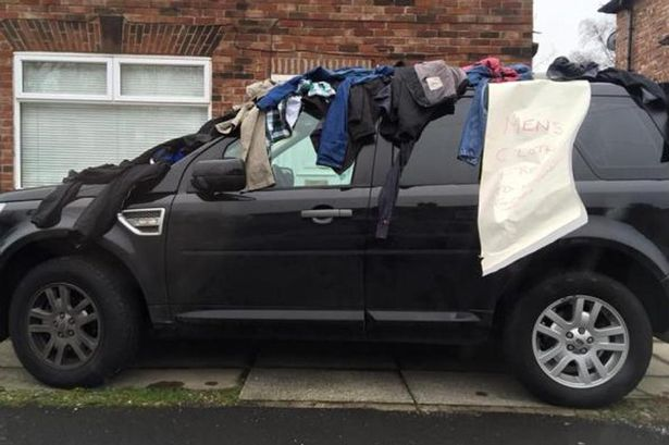 Clothes-on-top-of-a-car-with-a-sign-giving-them-away-for-free