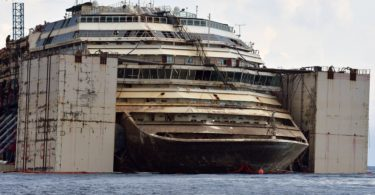 A picture shows the Costa Concordia cruise ship after being refloated using air tanks attached to its sides on July 21, 2014 at the Giglio Island. The Costa Concordia is due to be dragged away on July 22, 2014 from Giglio Island, where it crashed on the night of January 13, 2012 in a disaster that killed 32 people. The ship's final journey for scrapping in the port of Genoa in northwest Italy is set to take four days. AFP PHOTO / TIZIANA FABI        (Photo credit should read TIZIANA FABI/AFP/Getty Images)